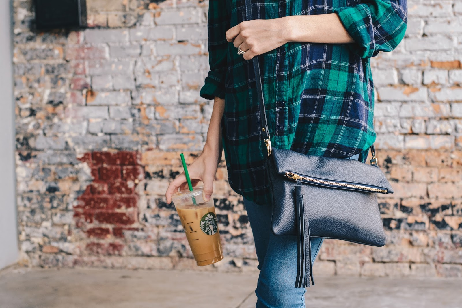 Weekend wear in a casual plaid top and a fringe cross body bag drinking a starbucks