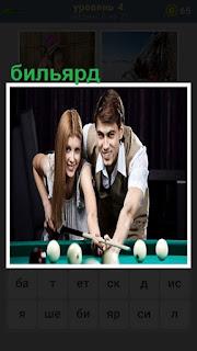 В бильярд играет женщина, а мужчина ей в этом помогает