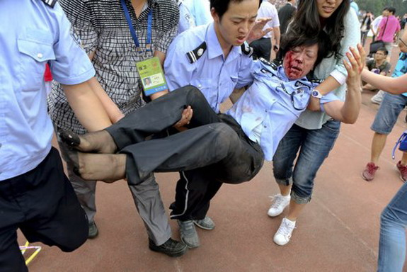 People carry an injured policewoman during a stampede by fans of David Beckham in Shanghai