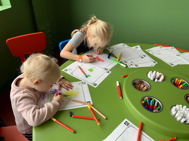 Children focused on colouring in their dinosaurs