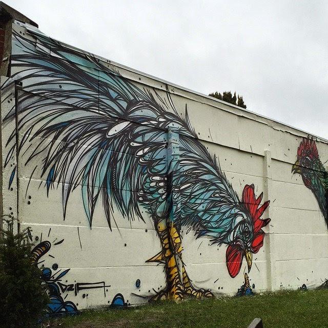 Gallo pintado en la pared de un jardín.