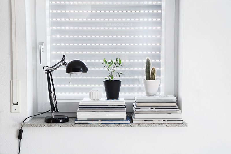 black and white modern scandinavian style windowsill decoration with task lamp, stacks of books, and plants