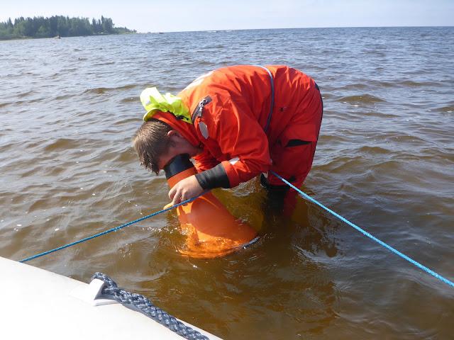 Pelastautumispukuinen henkilö katsoo veden alle vesikiikarilla, narun päässä on kumivene