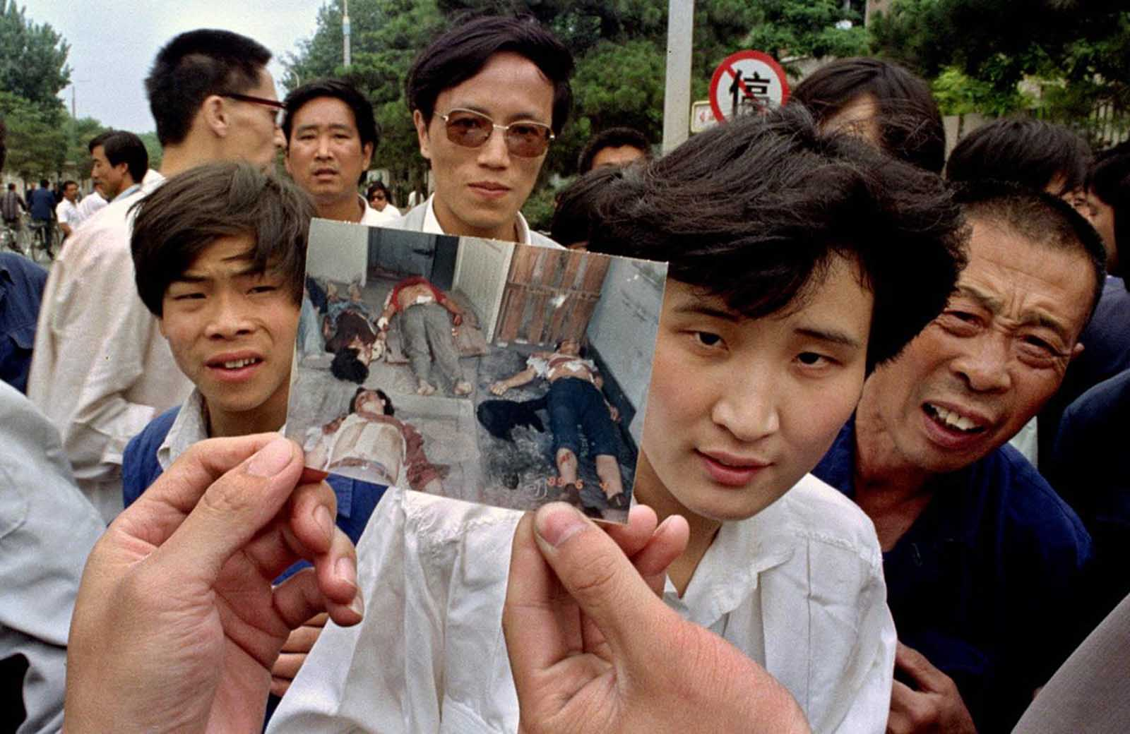 People on Chang'an Boulevard in Beijing hold up a photo that they described as dead victims of the violence against pro-democracy protesters on Tiananmen Square, on June 5, 1989.