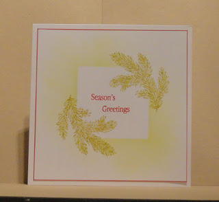 Christmas card, foliage branches and seasons greetings sentiment