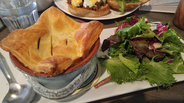 A plate containing a bowl savoury guinness steak and mushroom topped with a flaky pie crust beside a small salad of mixed greens.