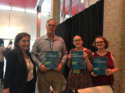 image: Four white people: Christina Nicolaidis,  John Elder Robison, Sara Luterman, and Shannon Rosa, holding up copies of the journal Autism in Adulthood.
