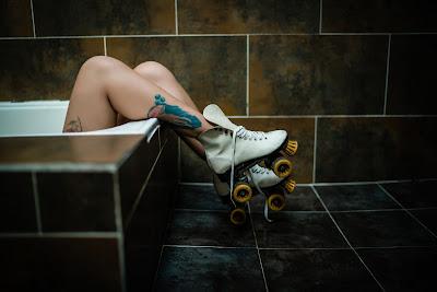 Chica acostada en la bañera con piernas fuera y patines