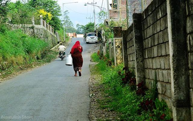 Bu Siamah meninggalkan Koperasi SAE Pujon usai menyetor susu perahannya