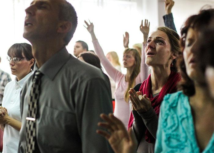 mulher orando na multidao mas nao e ouvida