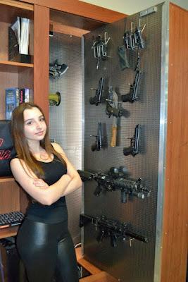 Junge Frau in Leggings mit großem Po zeigt Waffenschrank lustig