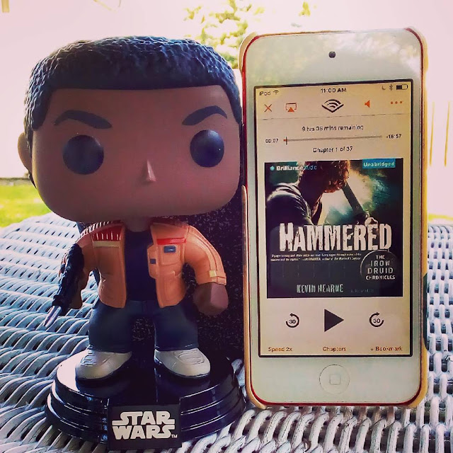 A large-headed Funko Pop bobblehead of Finn from Star Wars stands next to a white iPod with Hammered's cover on its screen. The cover features a sword-wielding redheaded man silhouetted against a blue and yellow light source.