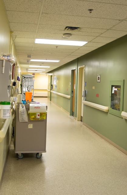 A hospital hallway with meds trolley and linnens stacked for patients.