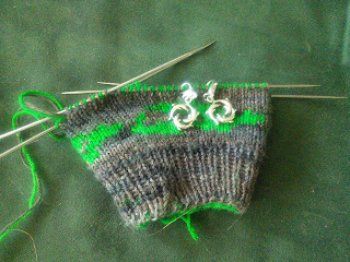 A double-knit mitten on double-pointed needles, knit in contrasting colours of green and brown yarn. There are two dolphin charm stitch markers on the needle, marking the increases for the thumb gusset.
