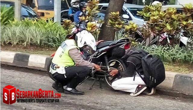 Foto Pak Polisi Ini Jadi Viral di Media Sosial. Ia Terlihat Membantu Remaja yang Rantai Motornya Lepas