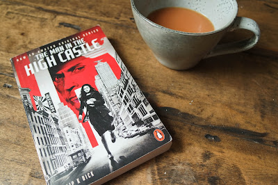 The Man in The High Castle by Phillip K Dick on Typewriter Teeth on a wooden background next to a cup of tea