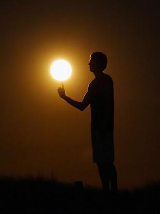 Güneşi bir top gibi parmağının ucunda çeviren sporcu