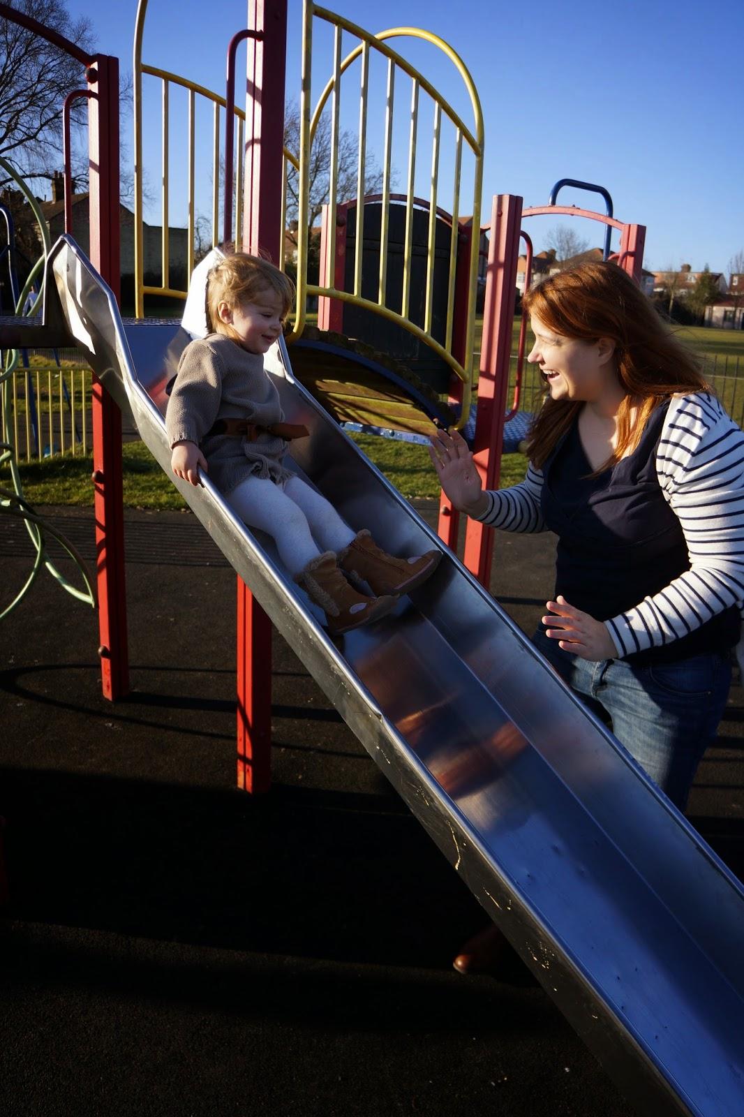 toddler girl sliding down a park slide