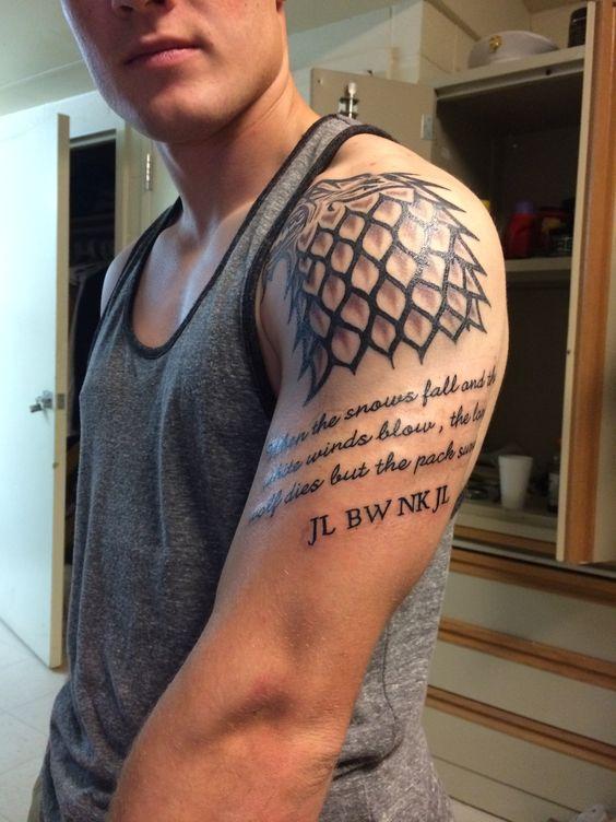 Chico en camiseta corta, lleva un tatuaje en el hombro, un tatuaje del lobo de la casa stark