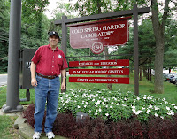 A photograph of me standing next to the entrance of Cold Spring Harbor Laboratory.