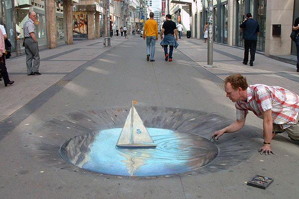 Kaldırımdaki çukurda birikmiş suda yüzen yelkenli bir gemi gösteren kaldırım sanatı resmi