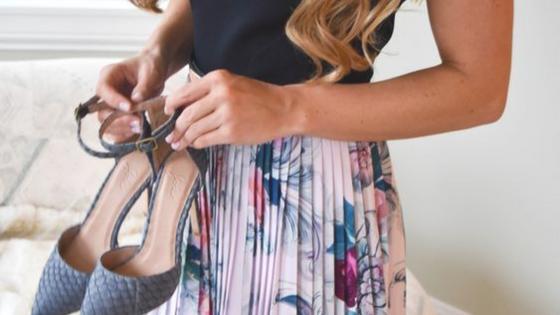 Imagem ilustrativa. Mulher com saia pregueada floral com uns sapatos rasos na mão