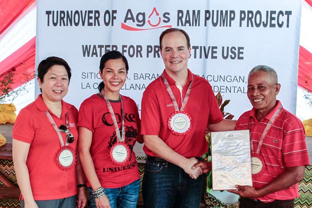 Coca-Cola executives turning over the water facility as part of its Agos Program