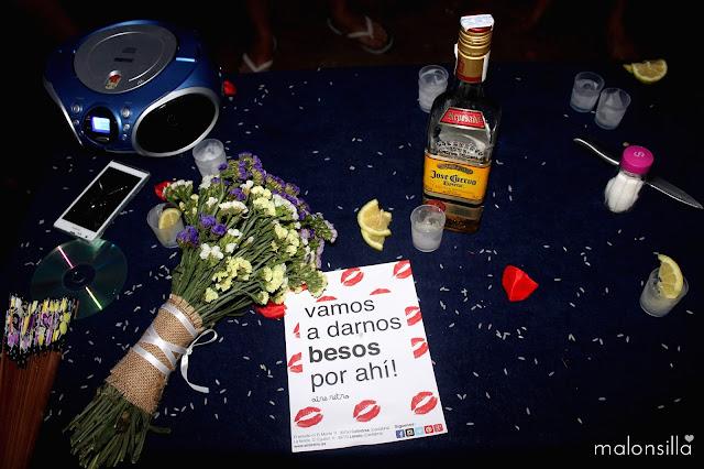 Mesa con los restos de la fiesta de boda, tequila José Cuervo, ramo de flores de siemprevivas, y cartel de Aire Retro, vamos a darnos besos por ahí