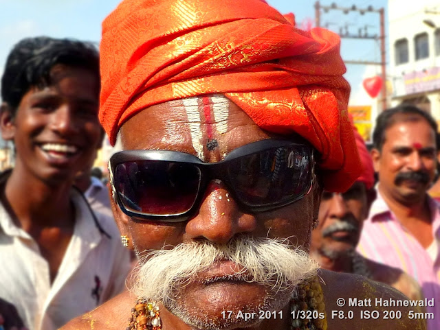 Facing the World, © Matt Hahnewald, street portrait, Dravidian people, South India, Madurai, Chithirai festival, headshot, Hindu man, Vishnu sign on forehead, sunglasses, red turban