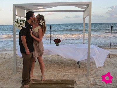 Casamiento. Novios besándose junto al altar en la playa