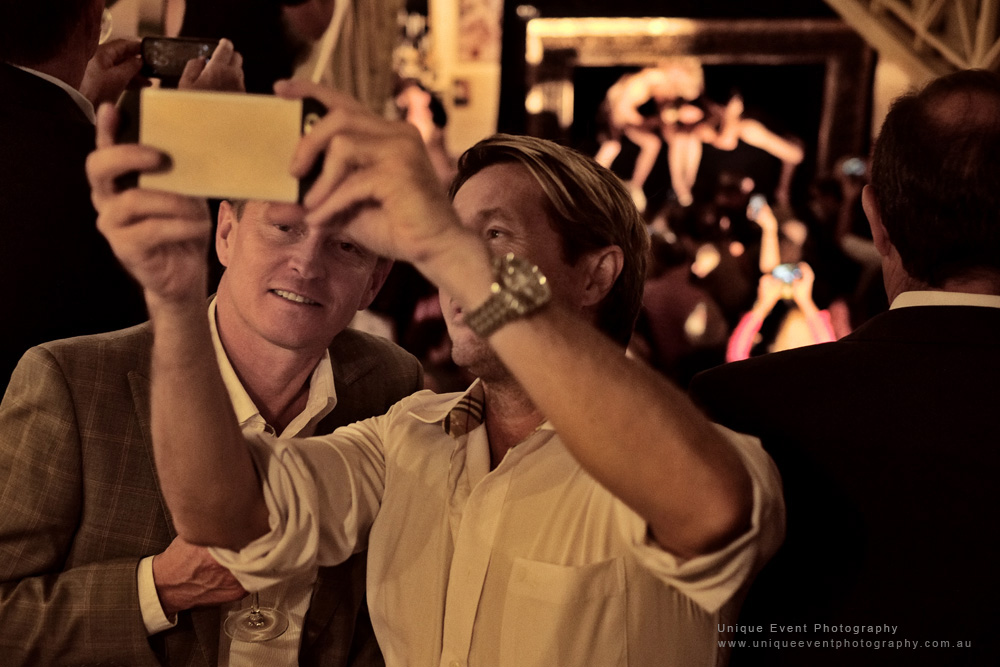 Double selfie with 'life models in frame' performance in background. The Billich Gallery 30th Anniversary 'Erotica' Party - Photographed by Kent Johnson for Unique Event Photography.