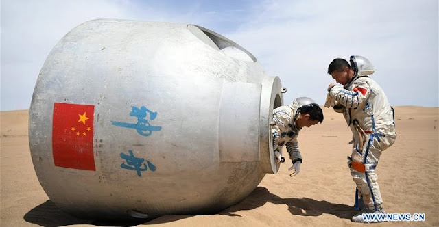 Taikonauts Nie Haisheng (L) and Liu Wang exit from a re-entry capsule during a wilderness survival training in the Badain Jaran Desert in northwest China's Gansu Province, May 17, 2018. Credit: Xinhua