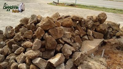 Pedra moledo com tamanhos variados e tom amarelado, para construção de torre de pedra.