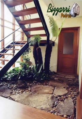 Pisadeira de pedra, com pedra moledo tipo chapada, na execução do paisagismo com pedregulhos do rio em jardim de inverno, em baixo da escada de madeira, em residência em condomínio em Atibaia-SP.