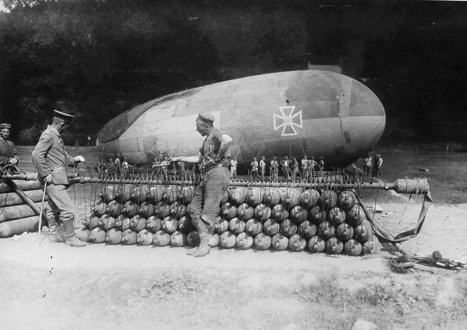 German soldiers attend to a stack of gas canisters attached to a manifold, inflating a captive balloon on the Western front.