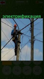 мужчина на столбе с проводами занимается электрификацией