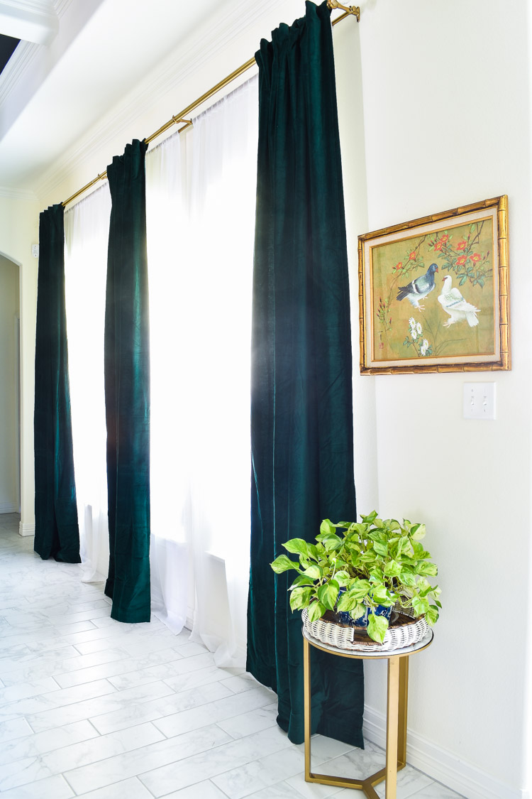 Extra long dark green curtains hanging in a living room space with white walls and marble tile floors and gold decor.