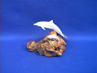 pair of dolphins figurine on burled wood by john perry
