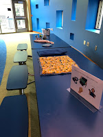 looking down long blue folding table with lap pads and fidgets on top, beside wall of various geometric shaped windows