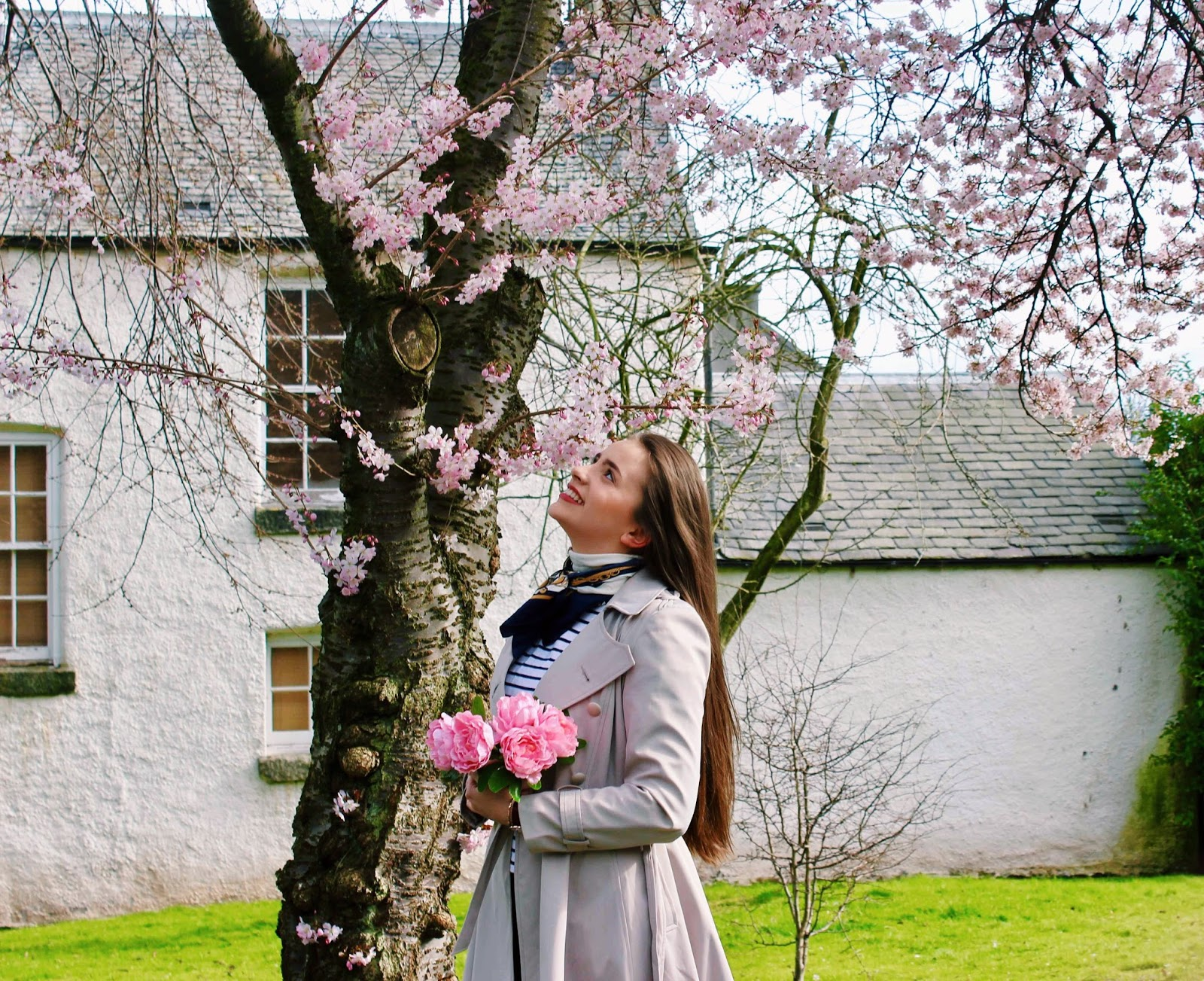 Girl with flowers under blooming cherry tree in spring