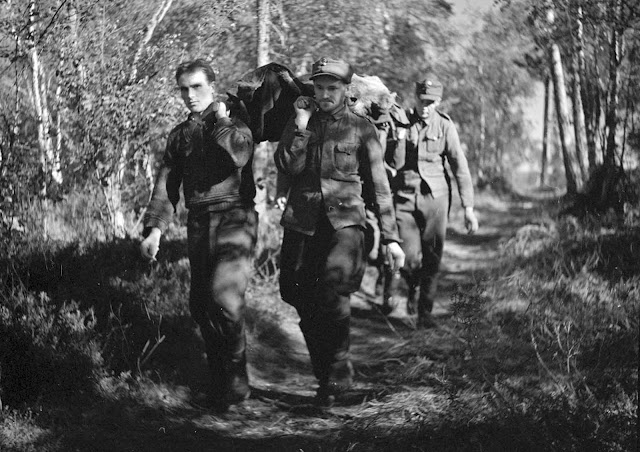 Soldiers carry a wounded man on a path.