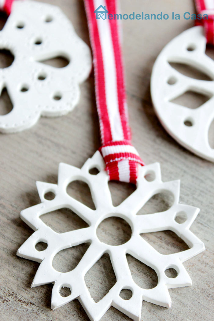 white snowflakes made of polymer clay with red ribbons