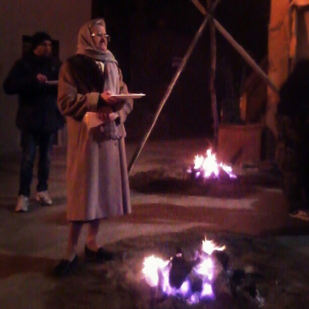 Old lady holding a plate with polenta next to an open fire