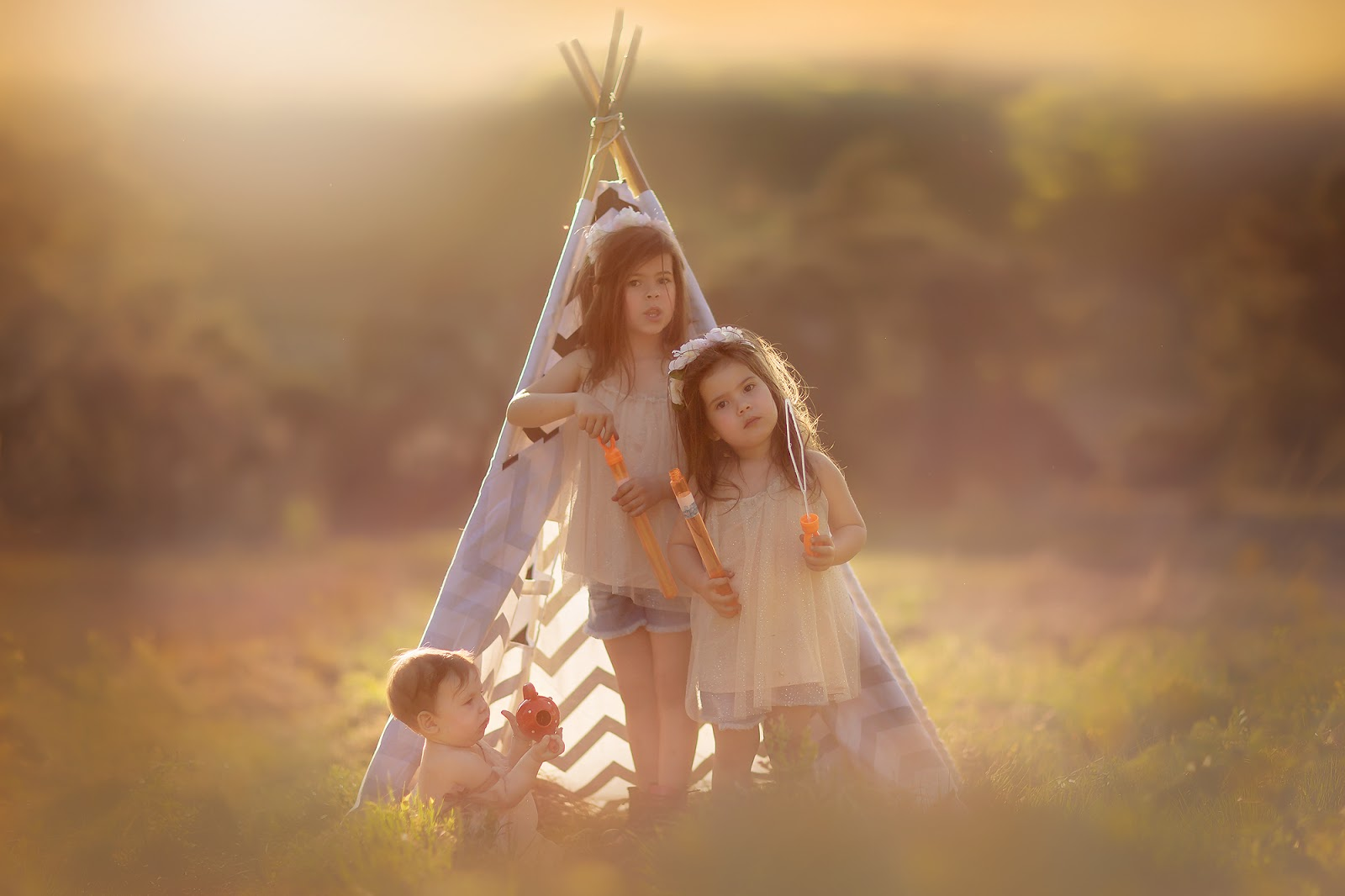 Image of three little sisters sitting in front of a tipi and playing during sunset by Willie Kers