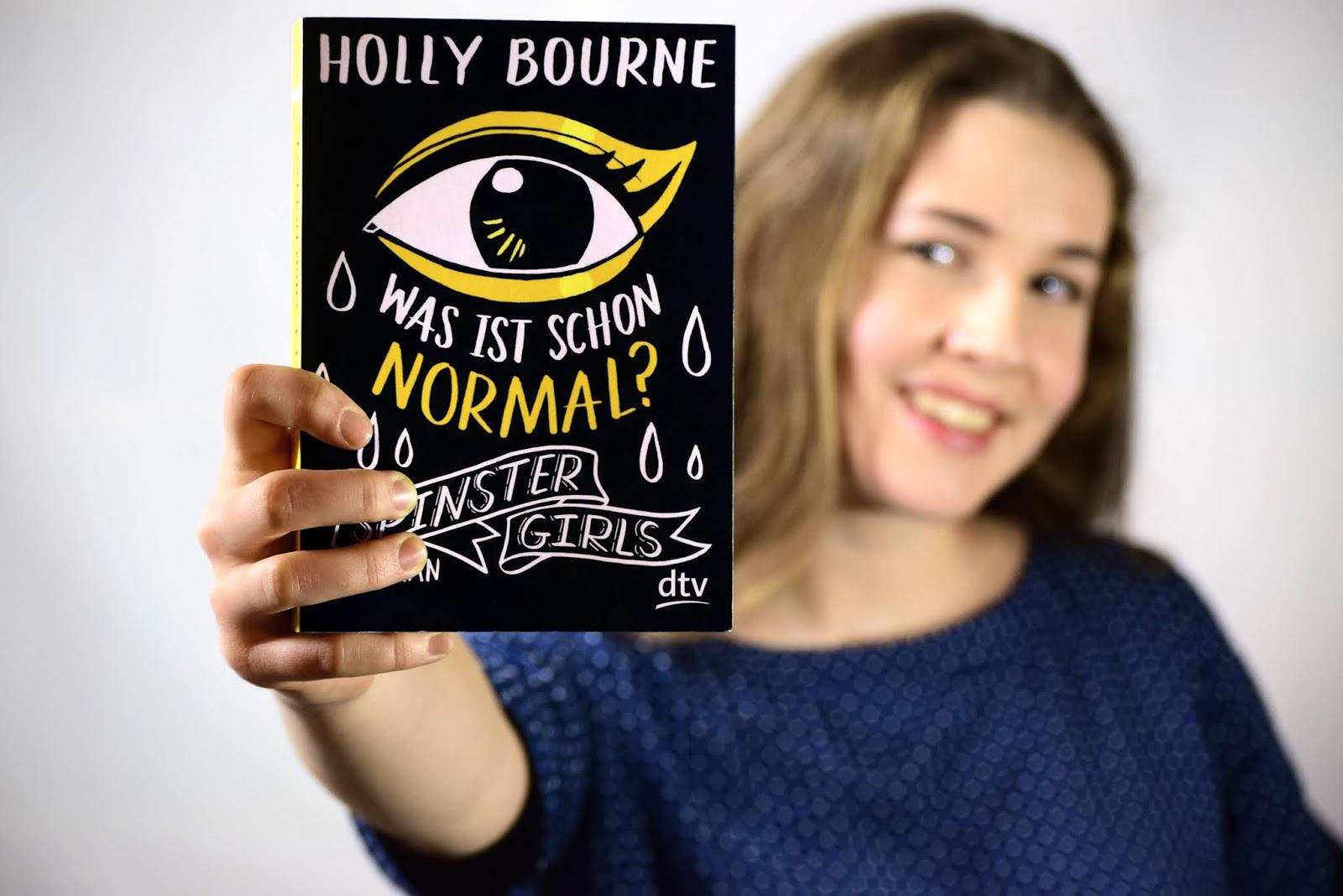 Mila posiert lächelnd mit dem Buch Spinster Girls – Was ist schon normal?