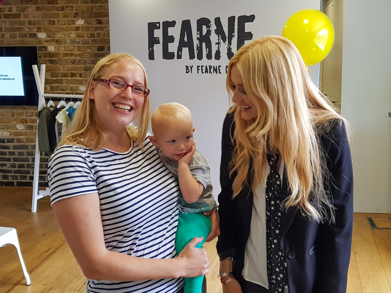 Me grinning at the camera, holding my toddler while Fearne Cotton smiles at my toddler