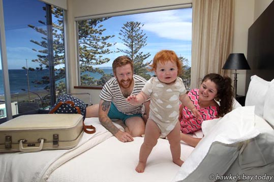 L-R: Dom Brown, their 14 month-old daughter Elliot, Rachel Burt, pictured in the Cape View Penthouse of The Dome, Marine Parade, Napier - winners of a luxury weekend for a Havelock North family, after a gastro outbreak in Havelock North, from a Hastings District Council water supply. photograph