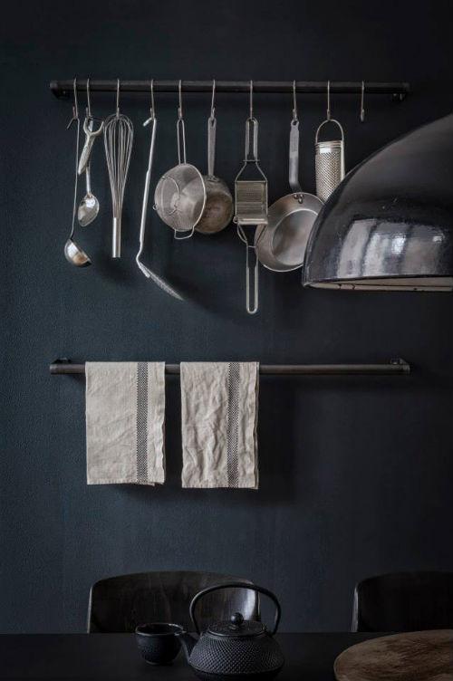 Die Wände dieser stilvollen Küche sind schwarz gestrichen. Davor kommen die Küchenutensilien schön zur Geltung