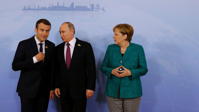 German Chancellor Angela Merkel poses with French President Emmanuel Macron (L) and Russia's President Vladimir Putin (C) prior to a meeting during the G20 Summit in Hamburg, Germany, on July 8, 2017.