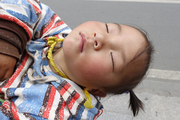 15+ Hilarious Pics That Prove Kids Can Sleep Anywhere - Child From Tibet Napping On The Back Of Her Mother While She Is Walking